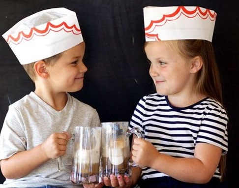 A young boy and girl toasting root beer floats
